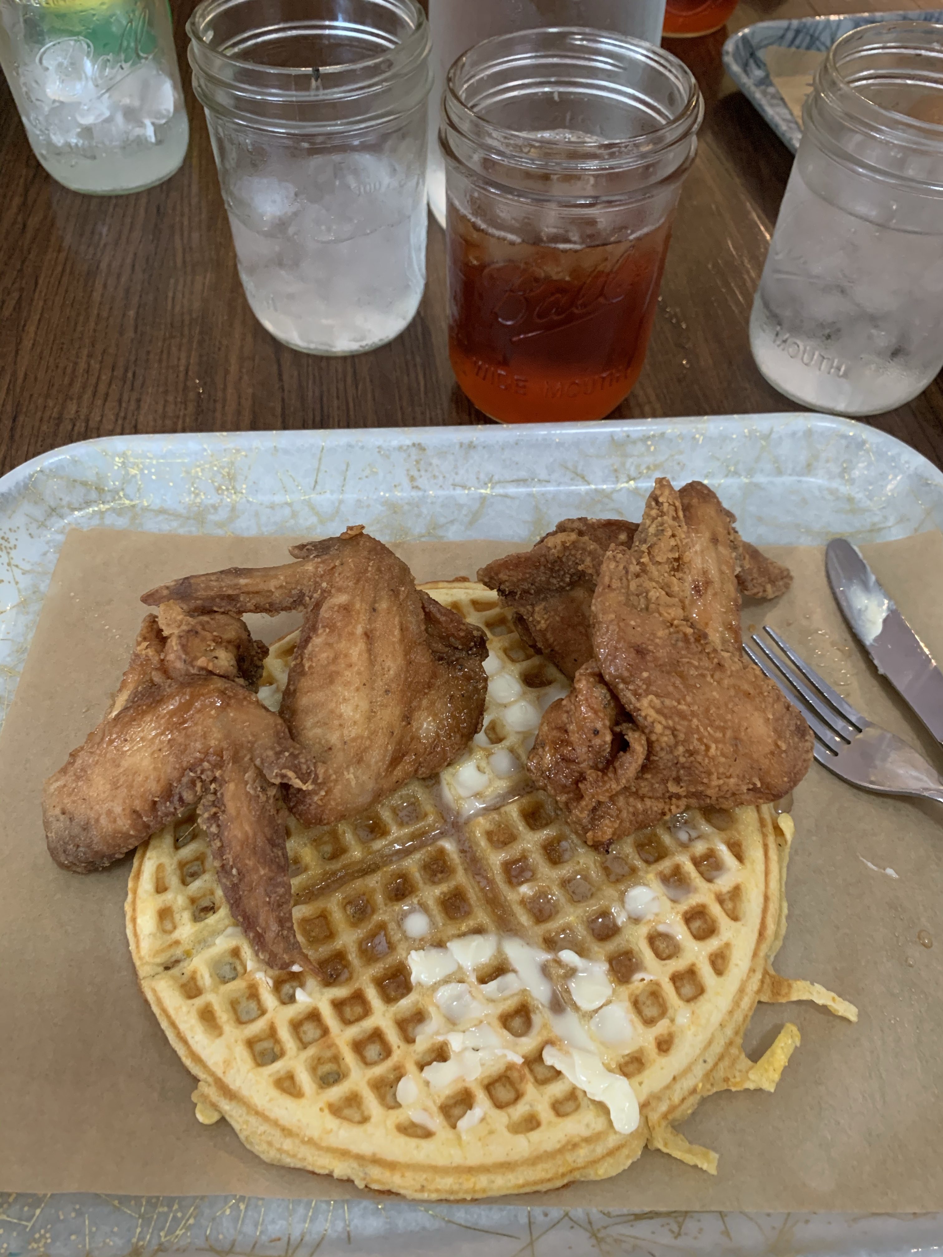 Four fried chicken wings and a southern style cornmeal waffle with butter and spiced maple syrup